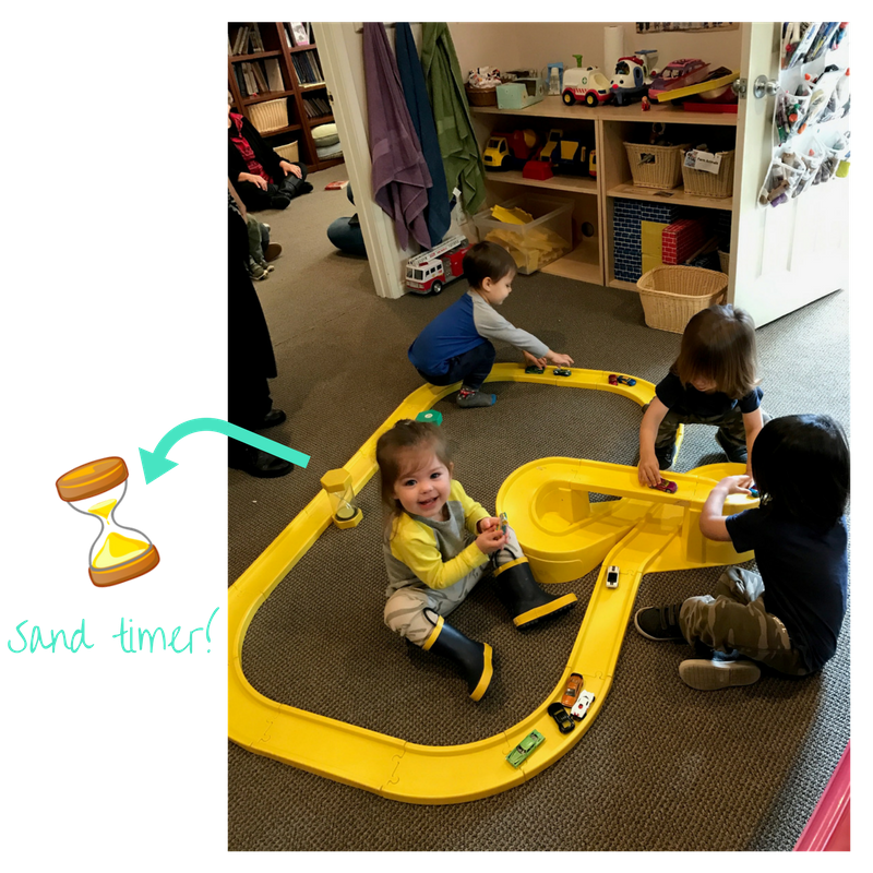 kids playing and learning to share using with sand timer at early childhood development class
