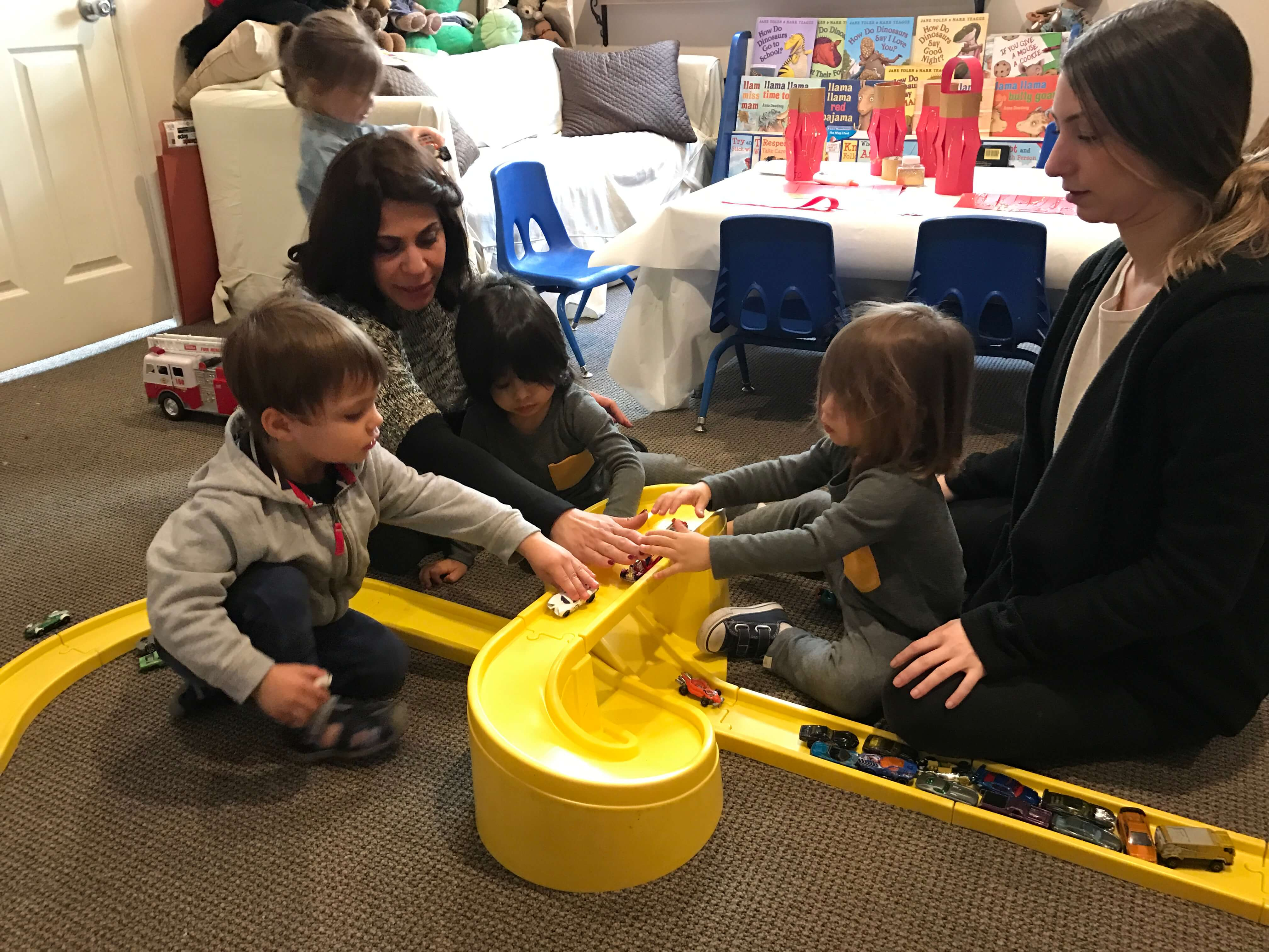 2 toddlers playing with cars on the trail, learning to take turns being supervised by adults at early childhood development class
