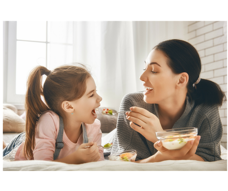 mother and daughter eating together fruits and yogurt