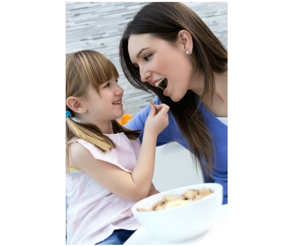 girl feeding mom healthy food