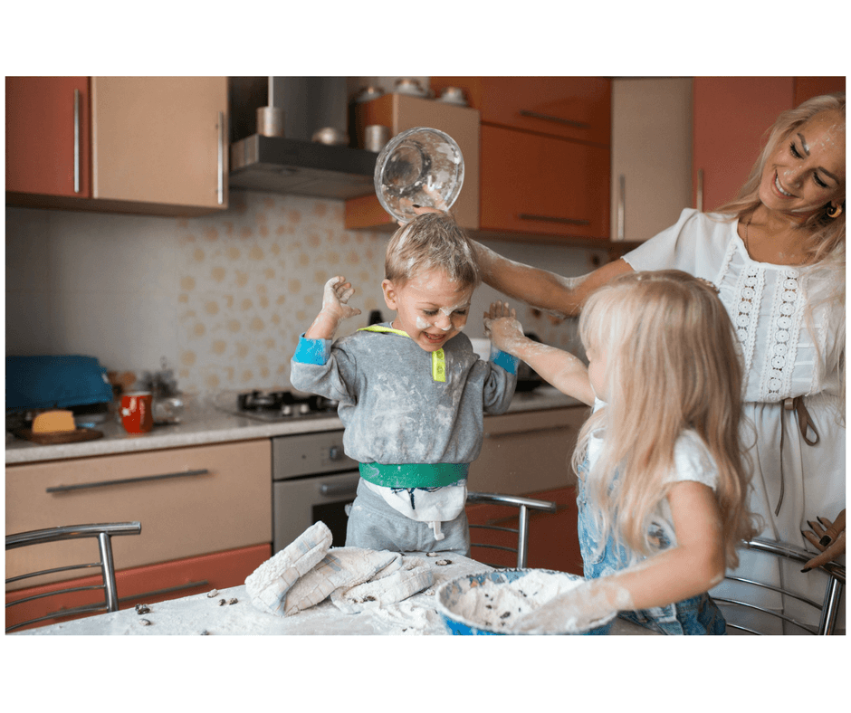 mother and 2 children messy playing in the kitchen with flour and bowls