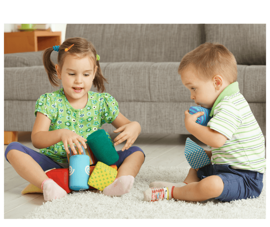 2 children playing together sharing toys