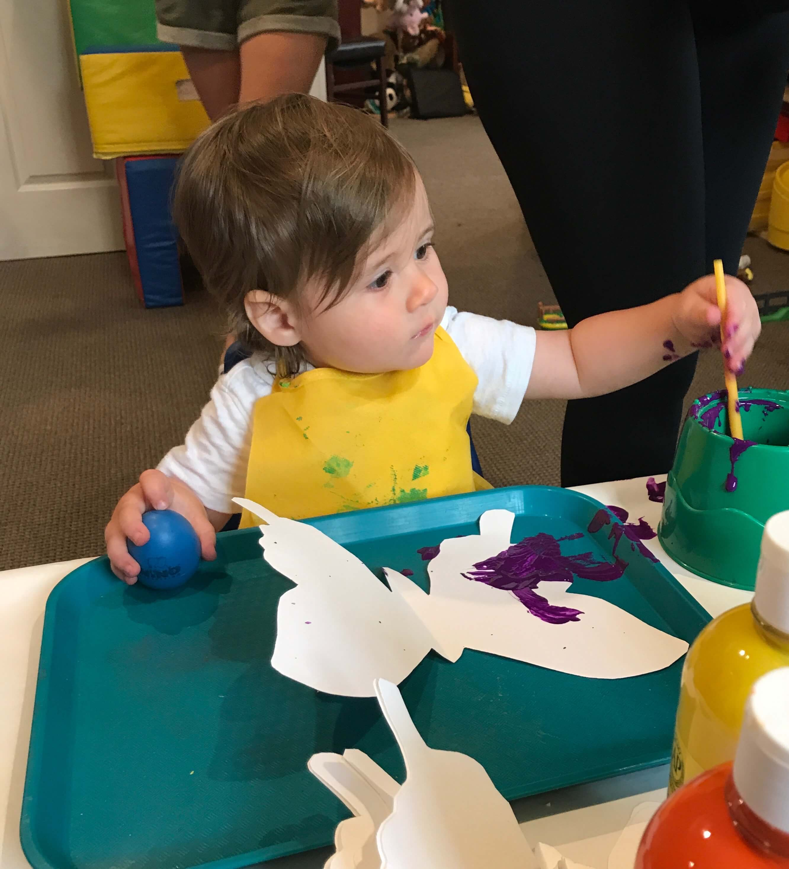 toddler painting butterfly shaped paper at early childhood development associates class