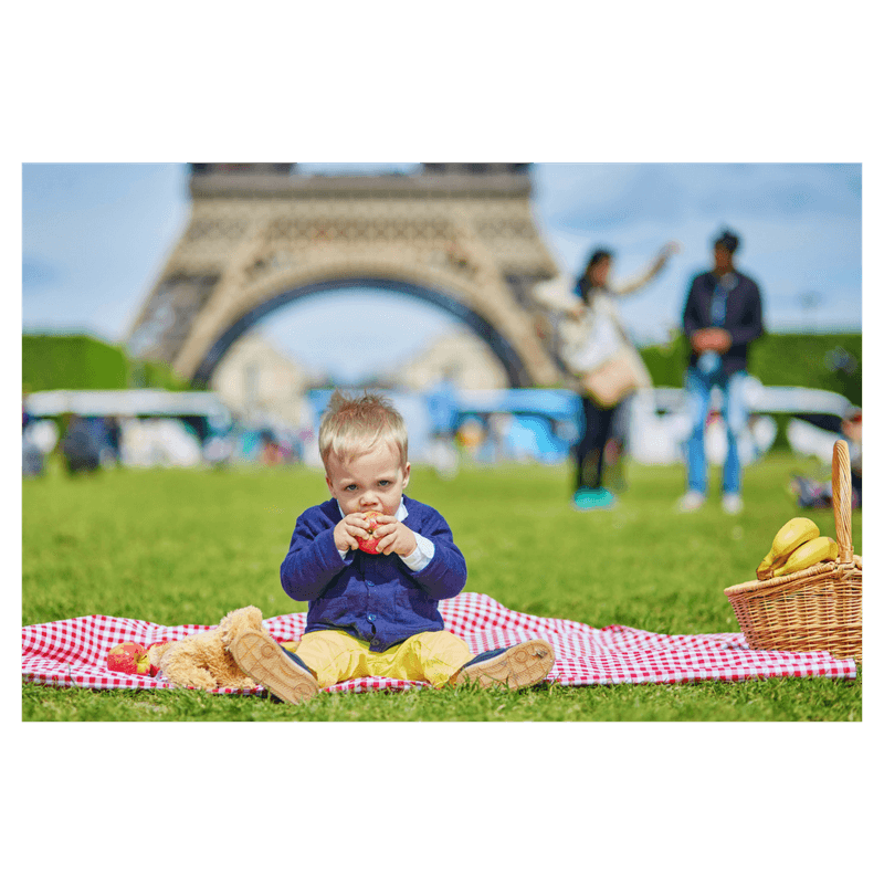 toddler sitting in blanket eating an apple in frot of eiffel tower in Paris