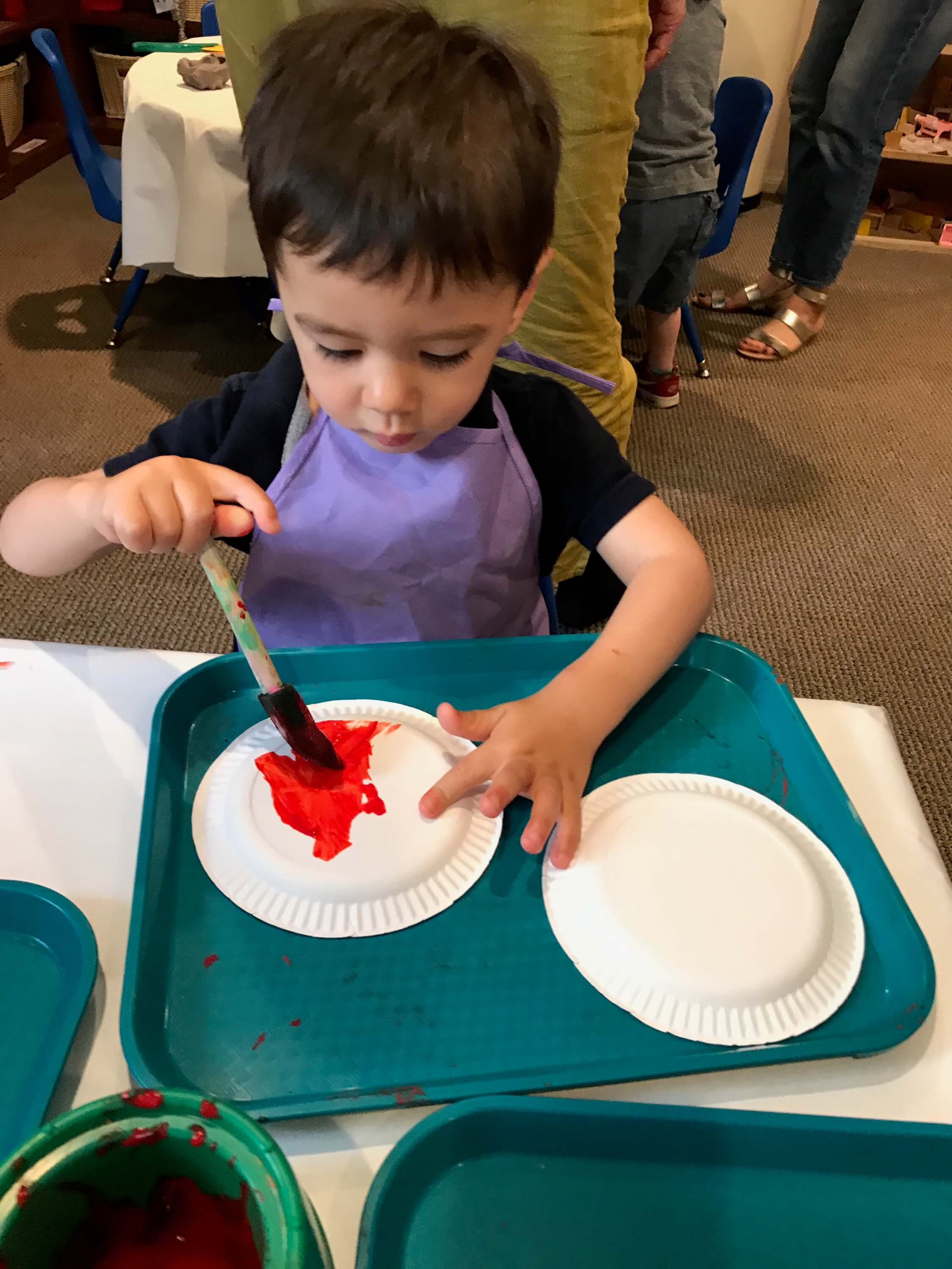 toddler paiting paper plate at early childhood development associates' class