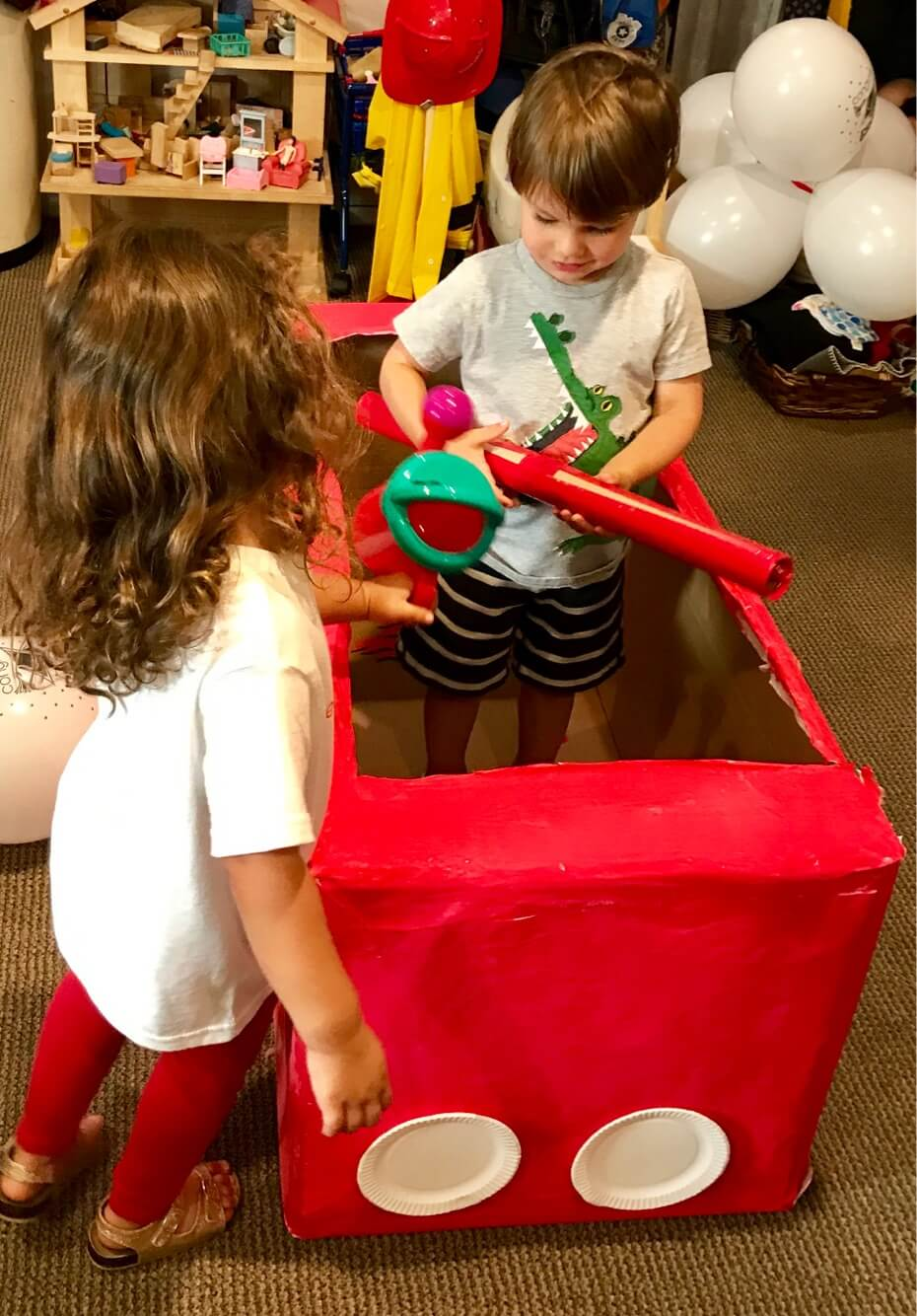 toddlers pretend playing inside firetruck at Early Childhood Development Associates' class
