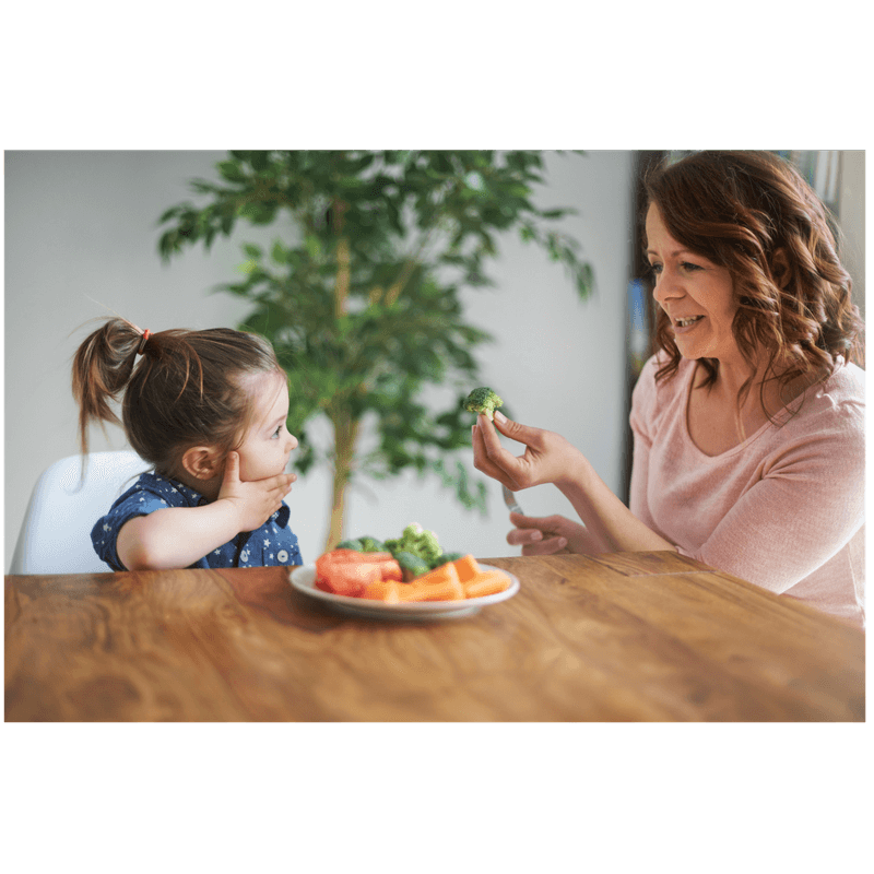 mom modeling how to eat healthy sharing a brocolli with toddler daughter