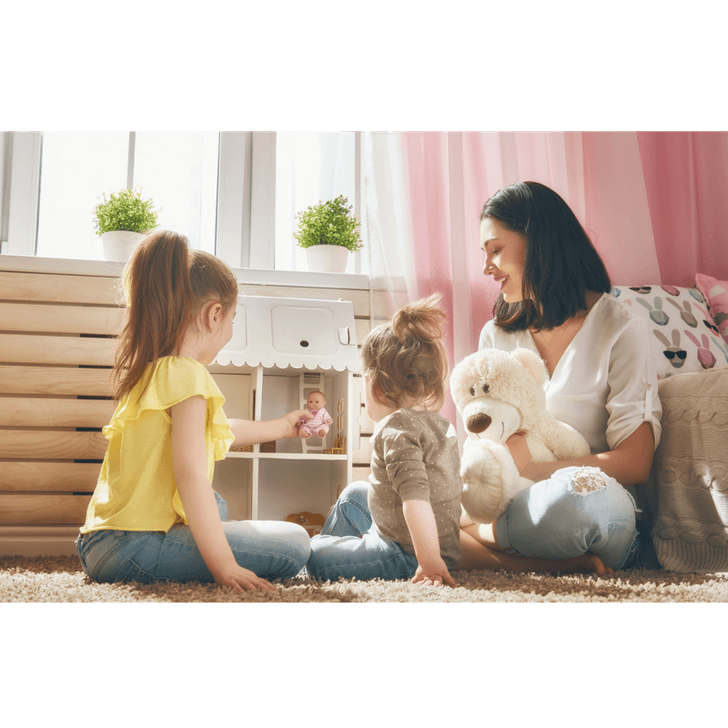 mother and 2 little girls playing doll house and talking