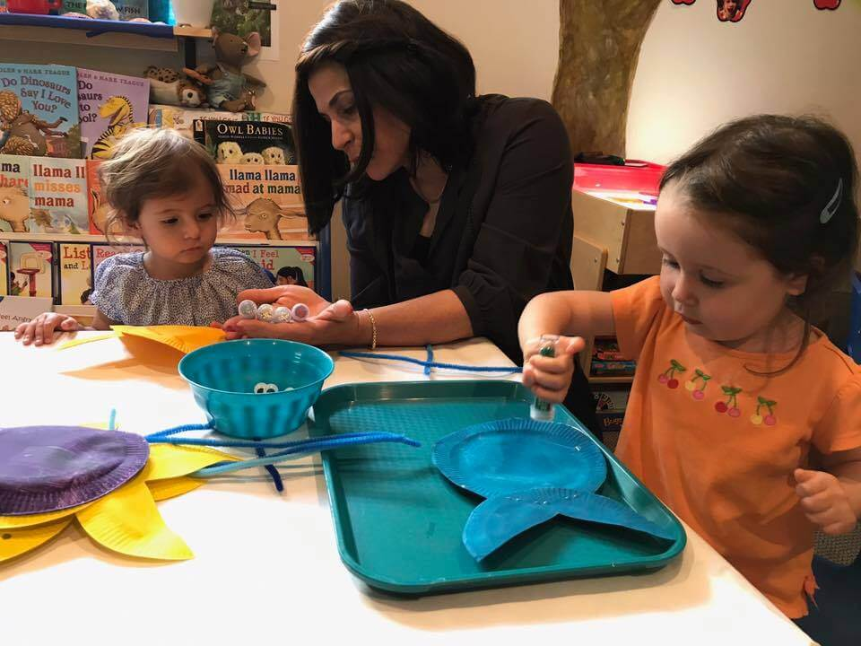 toddler painting fish at Early Childhood Development Associates's class