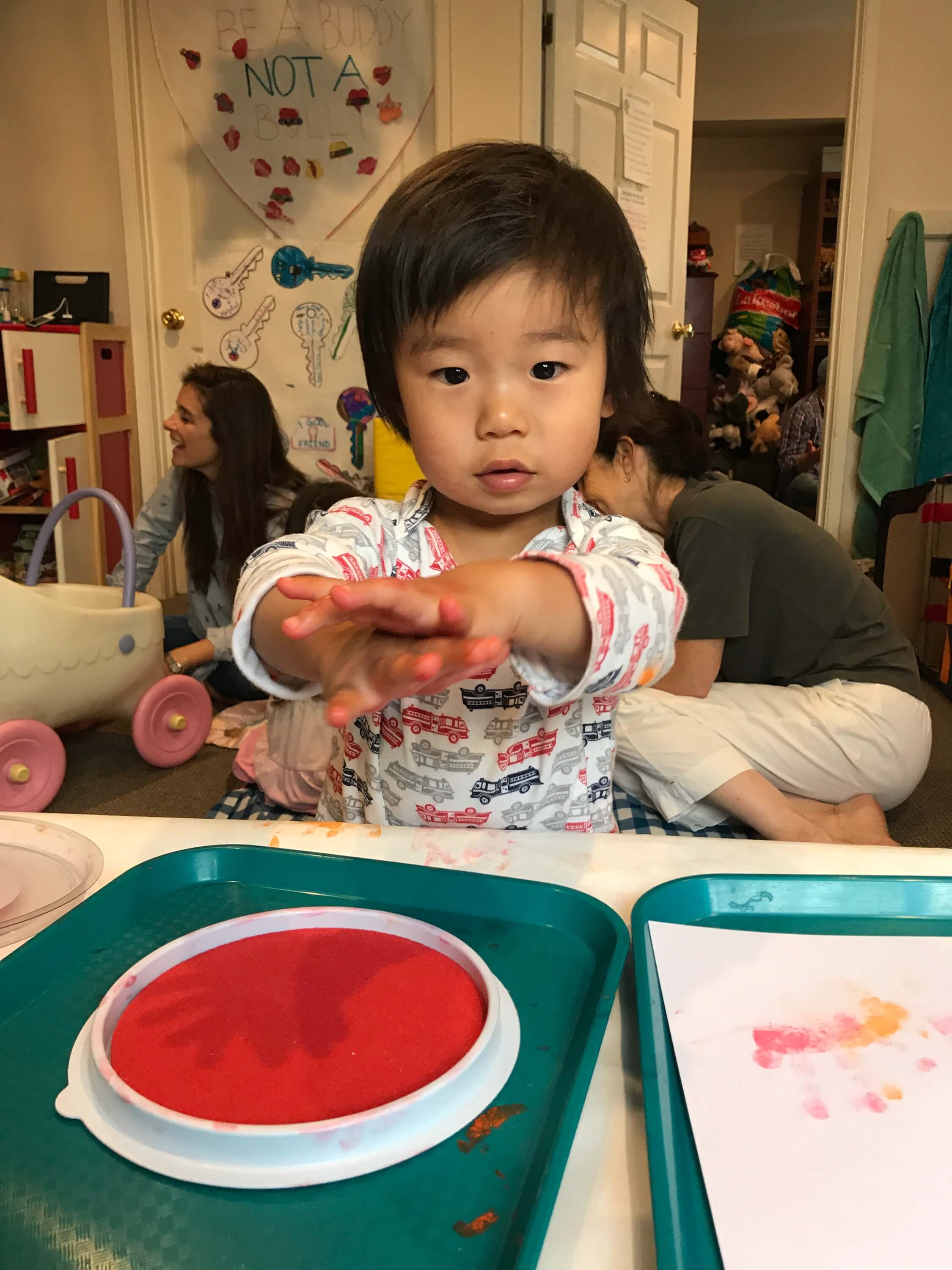 toddler making handprints with red paint at Early Childhood Development ASsociates' class
