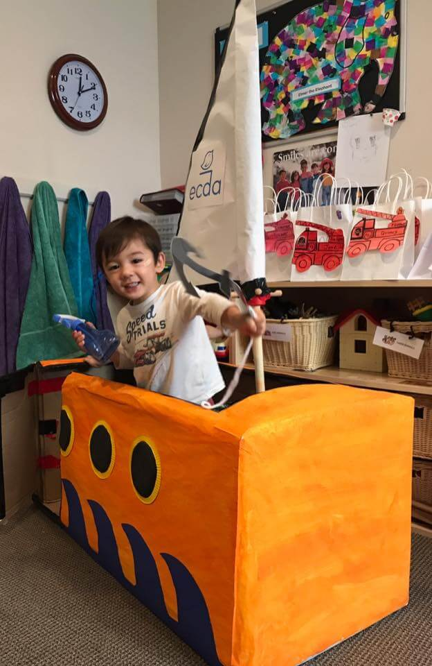 toddler playing in our big sail boat made from a cardboard box at Early Childhood Development ASsociates' class