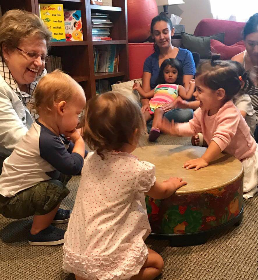 children playing the drum at Early Childhood Development Associates's class