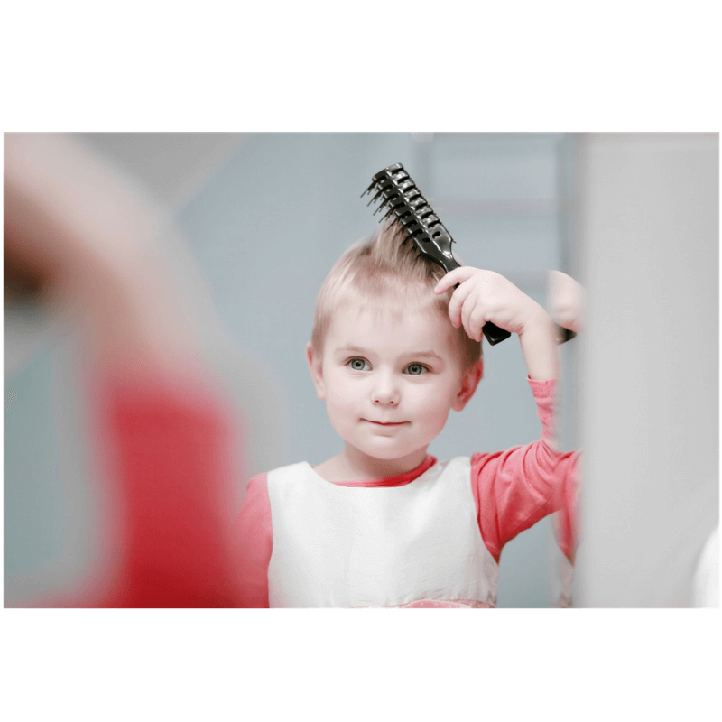little girl in front of the mirror brushing her hair before going to school in the morning