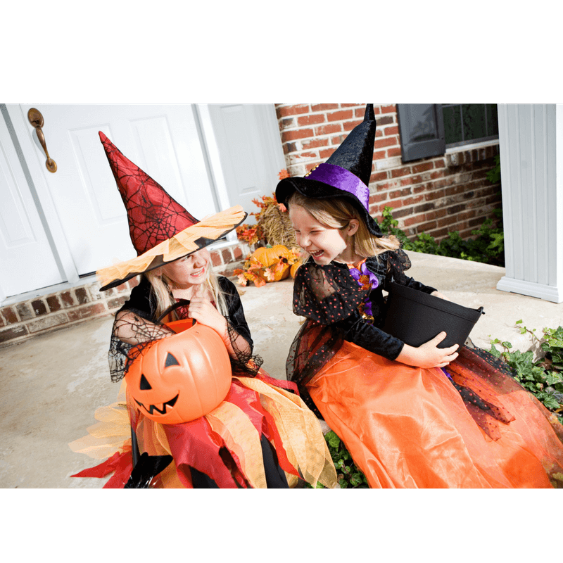 2 toddler girls wearing costumes looking happy after trick-or-treating