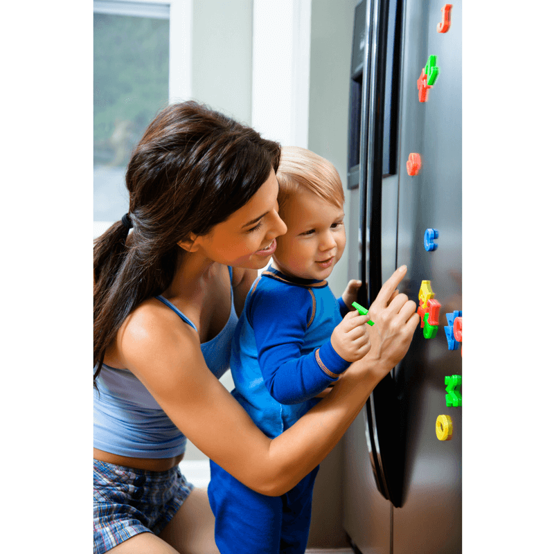 mother helping toddler son with magnets on the fridge