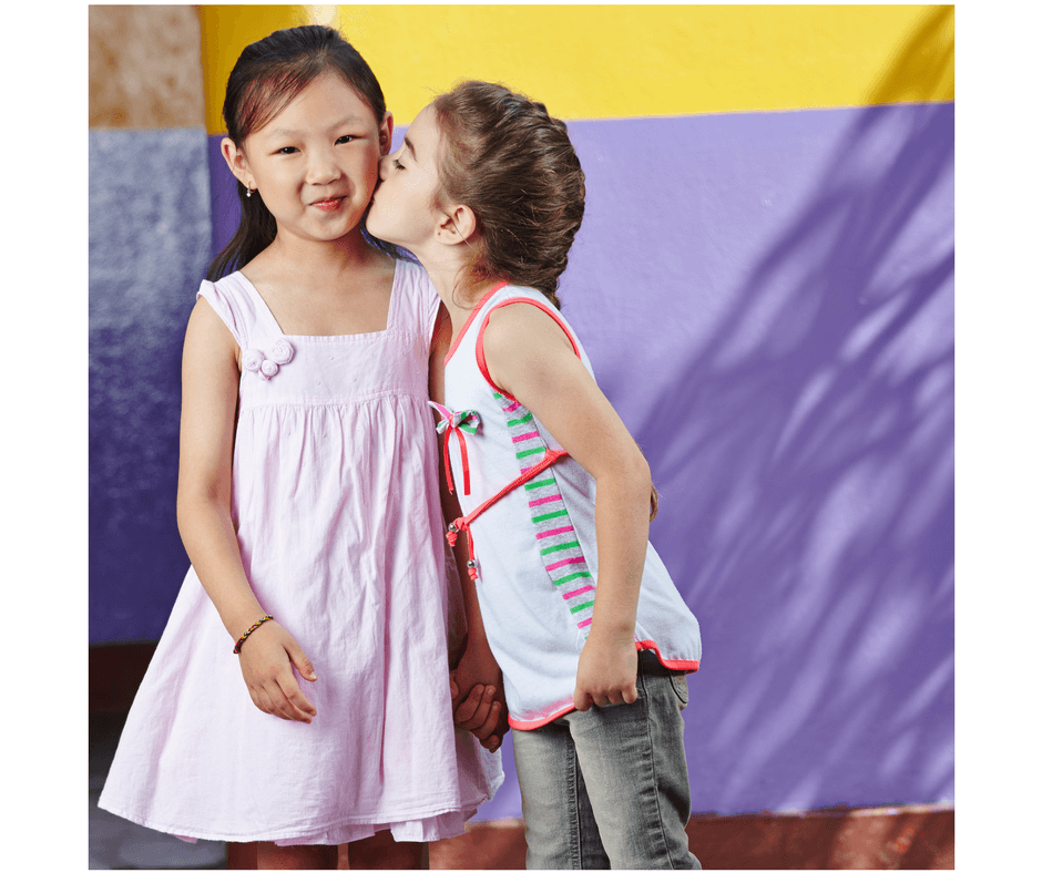 one toddler kissing another toddler on the cheek being a good friend