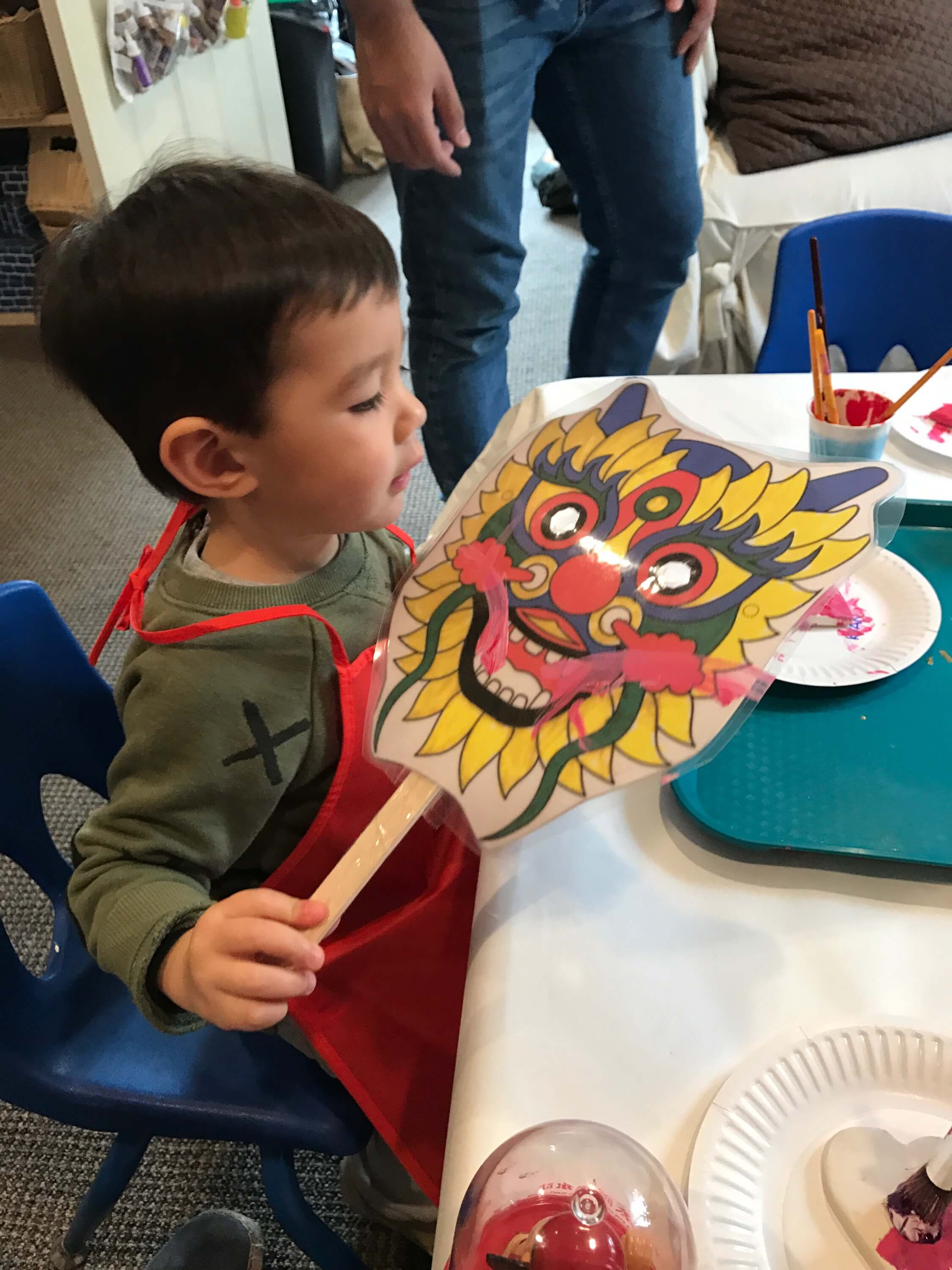 little boy holding chinese new year mask at early childhood development class