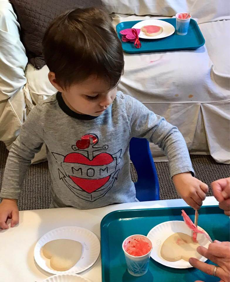 little boy frosting heart shaped cookies at early childhood development class