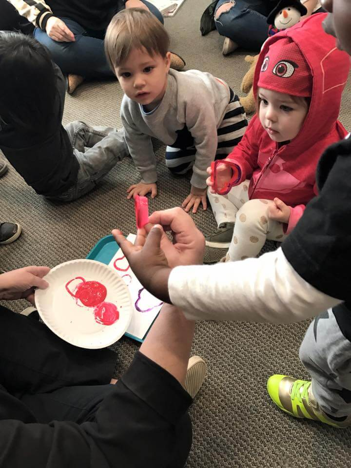 kids learning to paint hearts out of heart shaped cookie cutters at early childhood development classes