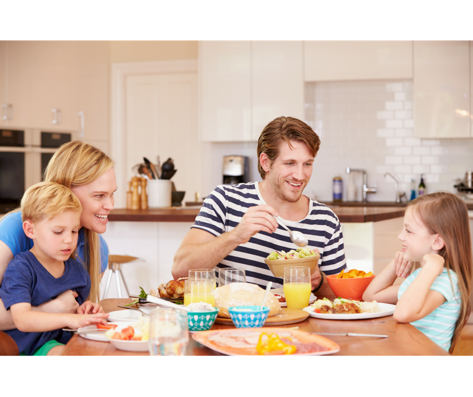 dad offering daughter food from the table while having a family meal