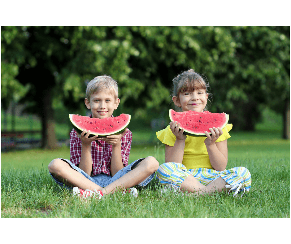 friends sitting side by side eating watermellon