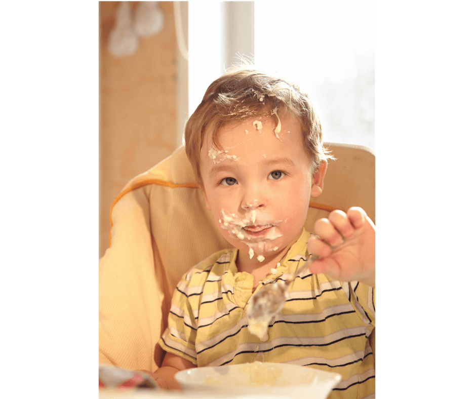 toddler making a mess while eating by himself