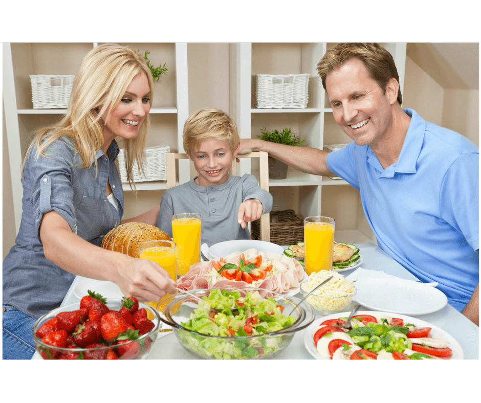 mom showing healthy food to toddler while having a family meal