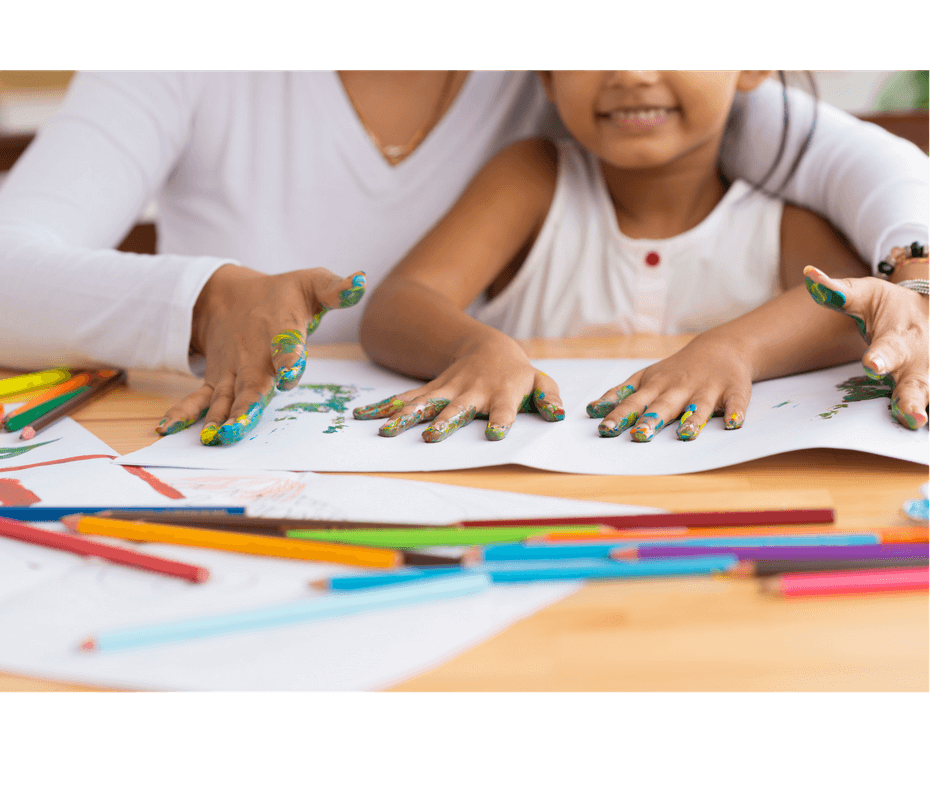mother and daughter playing with finger paint in their hands, tracing the hands