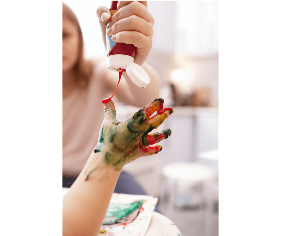 mother pouring paint in child's fingers for messy play