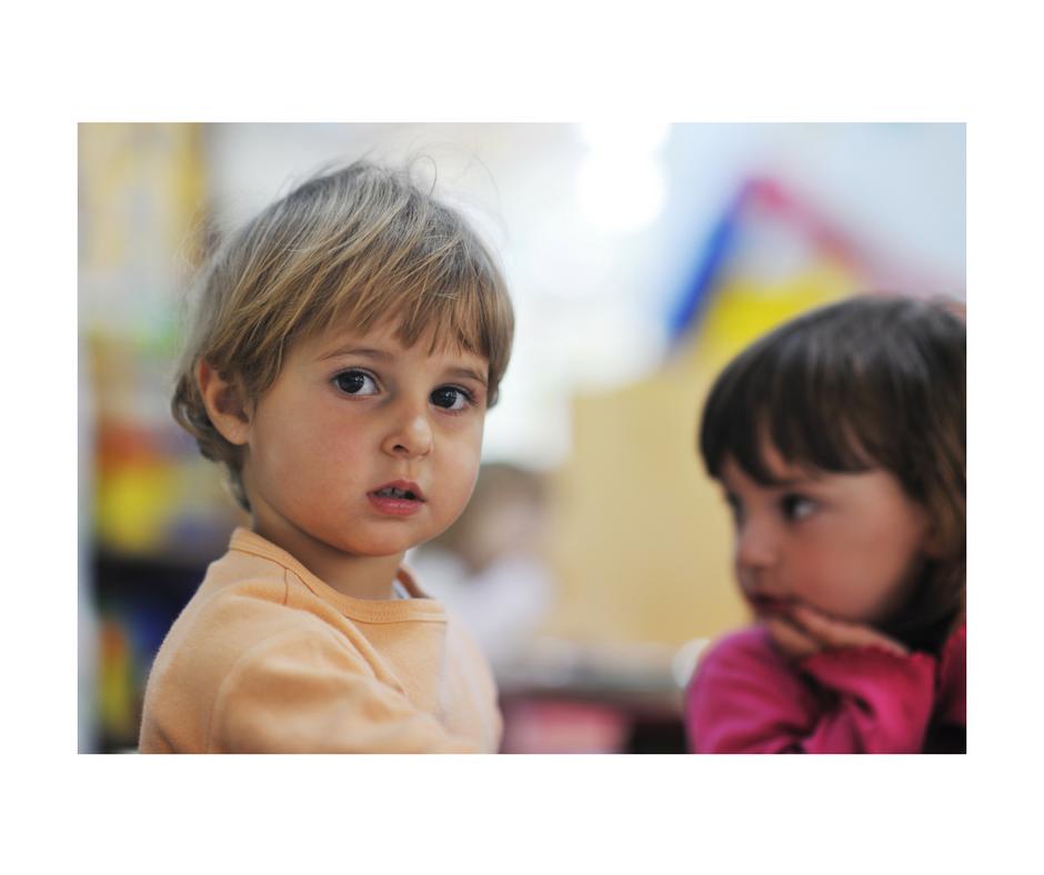 preschooler looking at the camera, another preschooler looking away