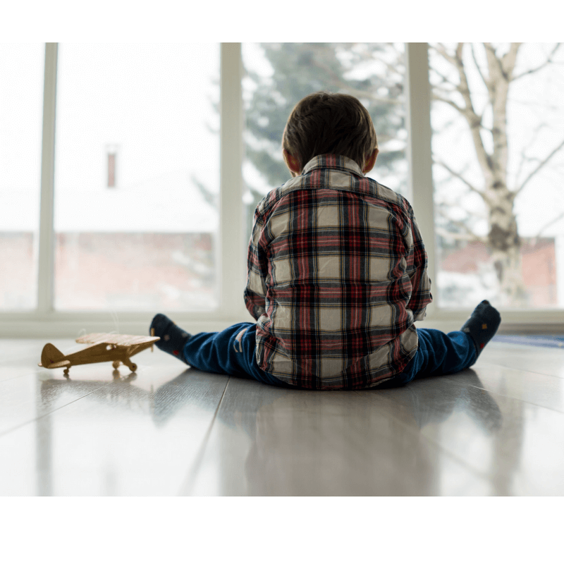 child facing window, seems lonely