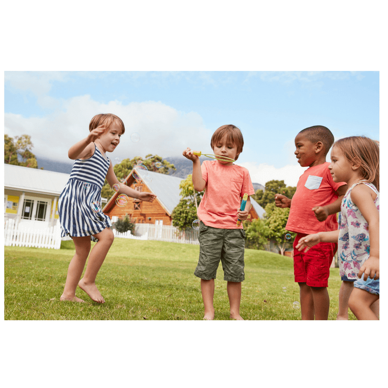 4 children playing together at park or school blowing bubbles