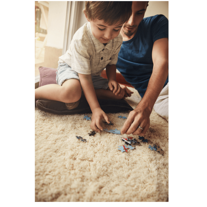 father and son sitting on the floor playing with cars