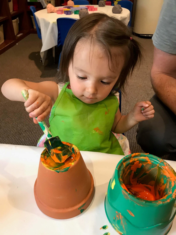 toddler paiting pot at early childhood development associates' class