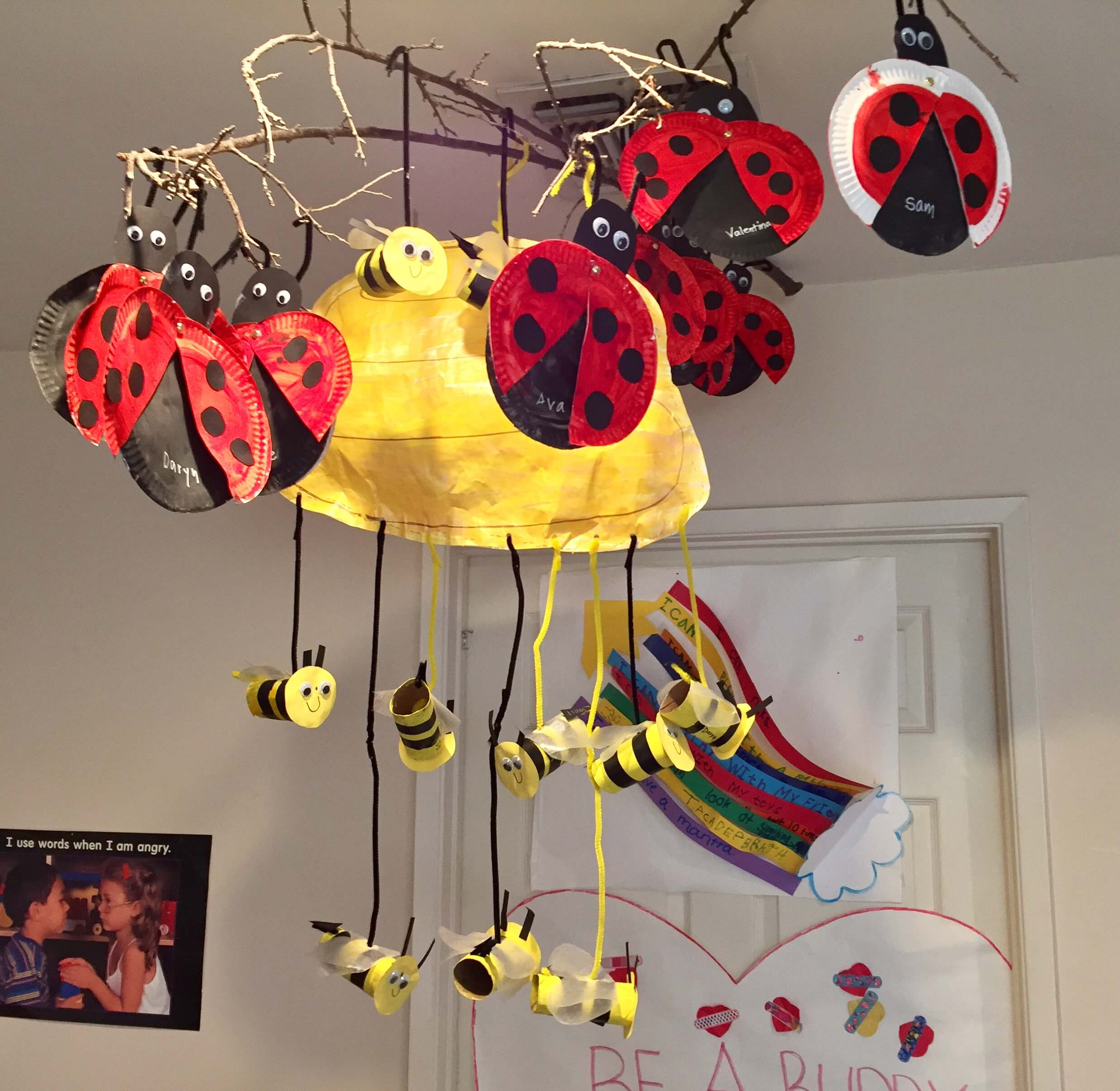 bugs made out of paper plates and toilet paper rolls hanging from ceiling at early childhood development associates