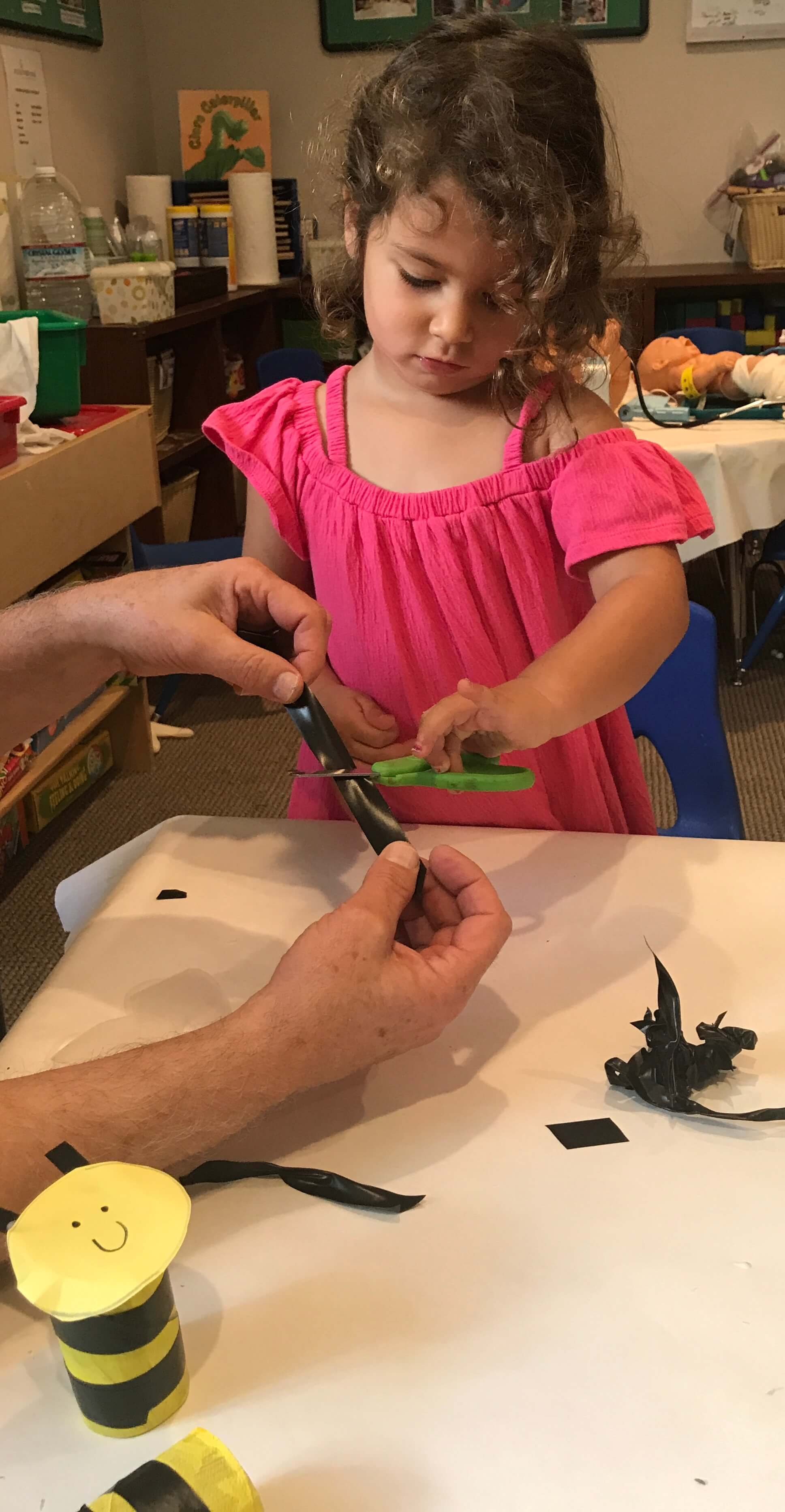 toddler learning to cut with scissors at early childhood development associates' class
