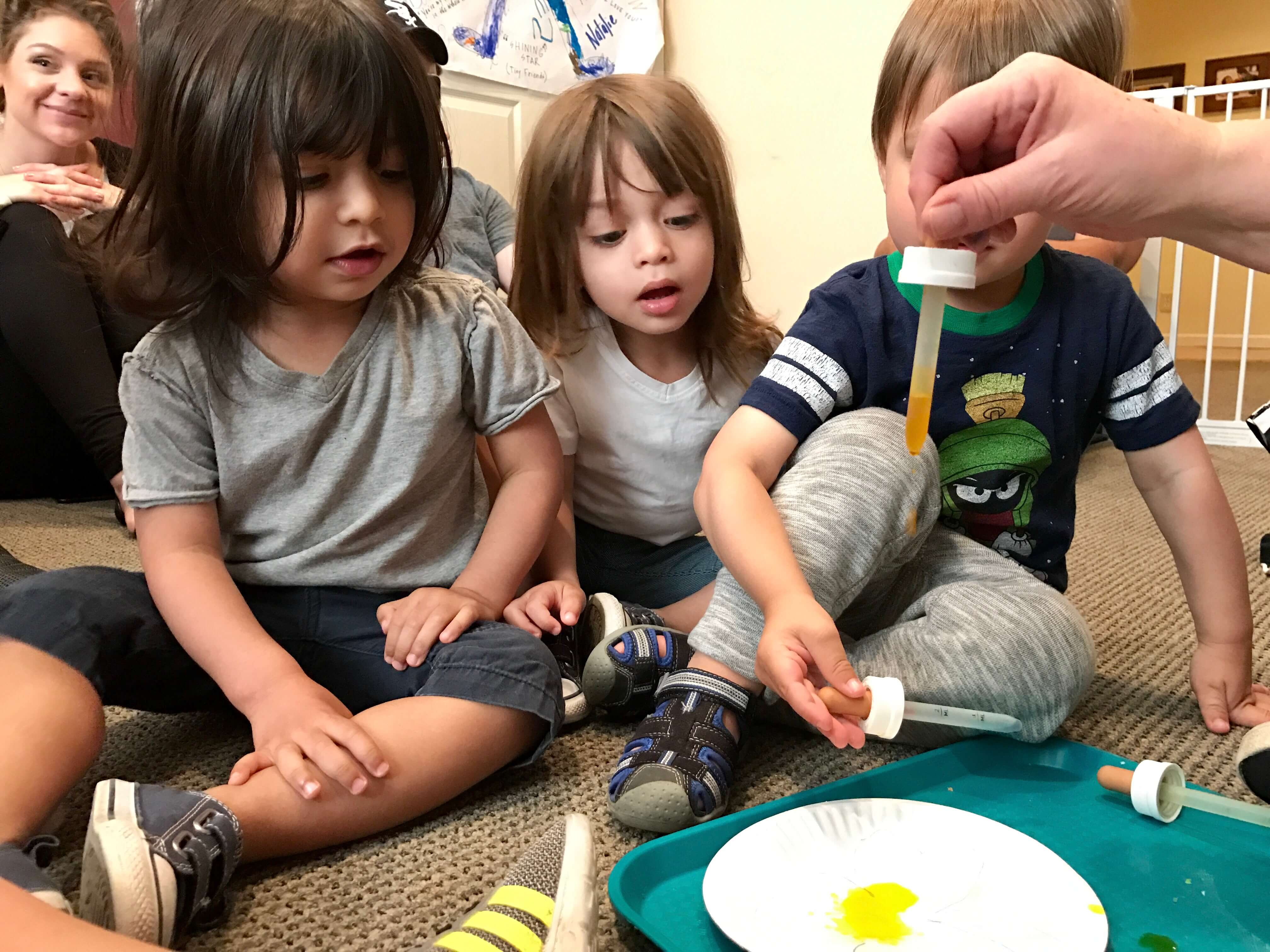 3 children learning to drop paint at early childhood dvelopment associates' class