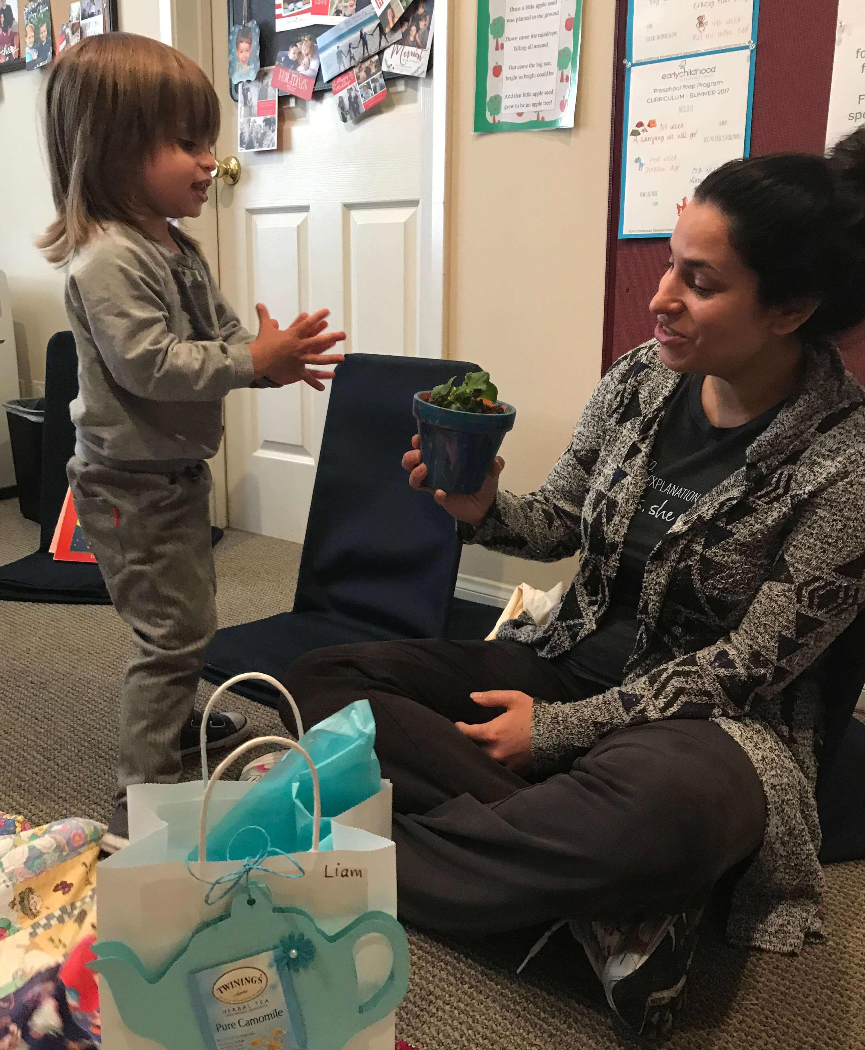 toddler giving mom a mother's day gift that he made at early childhood development associates' class