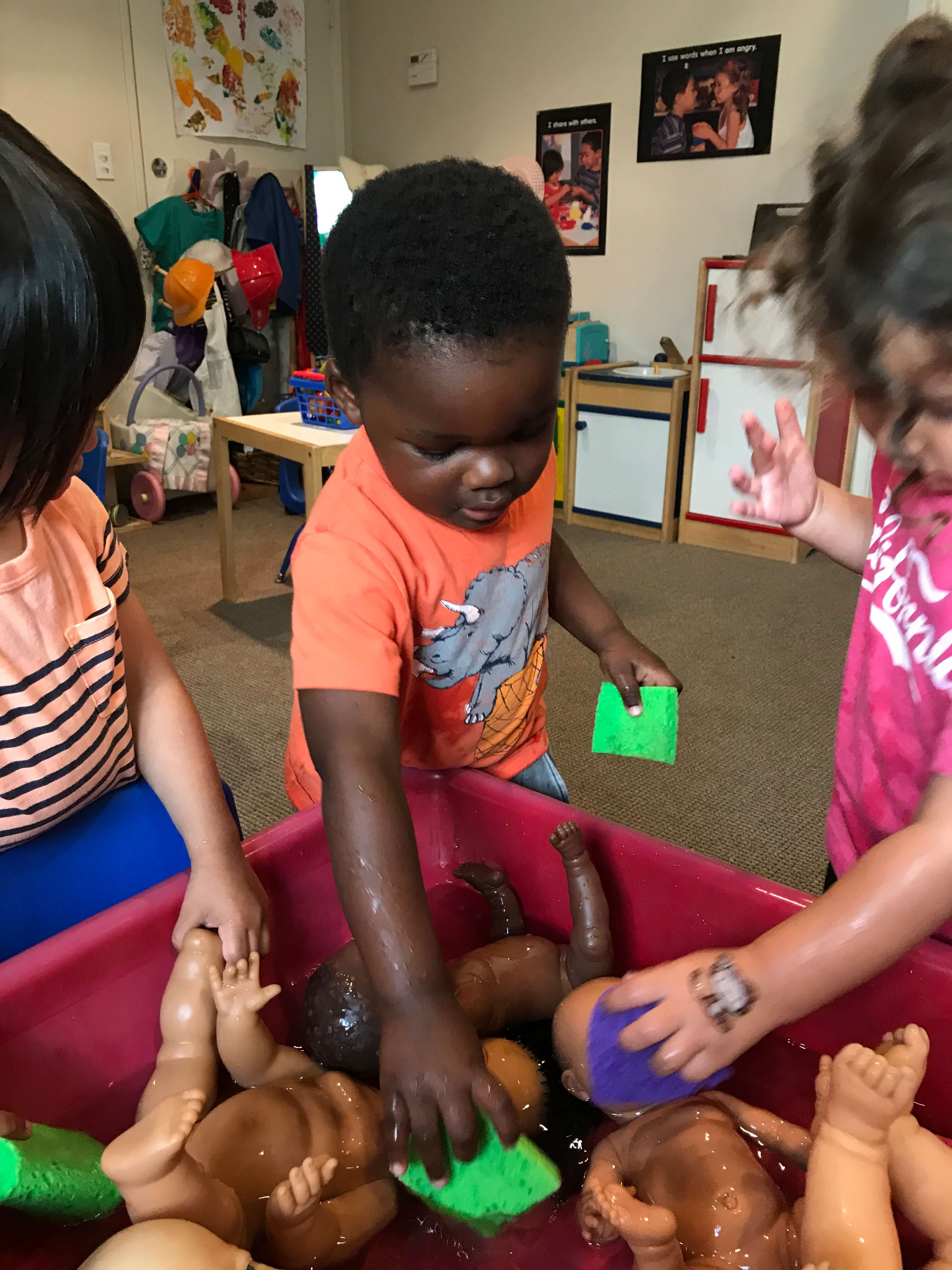 3 toddlers playing with water in sensory table at early childhood development associates