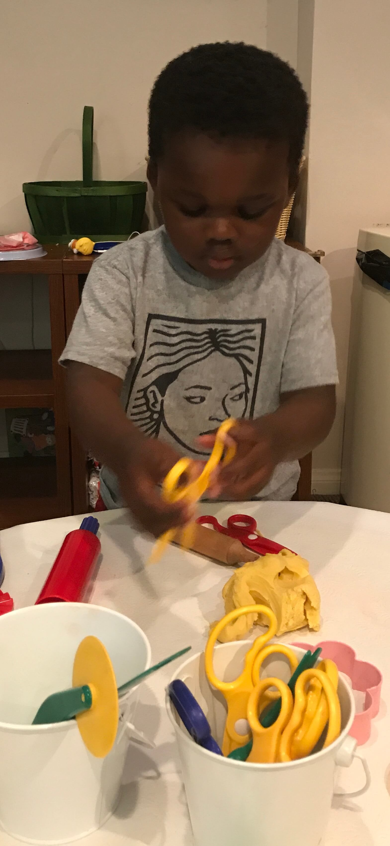 toddler using scissors at Early Childhood Development Associates' class