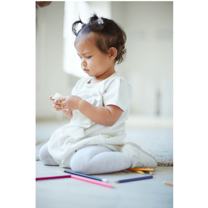 little girl playin on the floor with pencils and paper while waiting