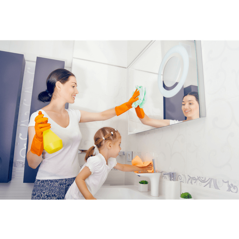 mom modeling how to clean mirror in the bathroom with toddler daughter