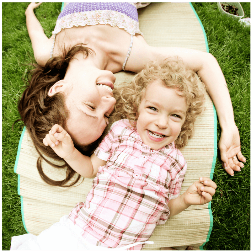 mother and daughter lying on the grass smiling