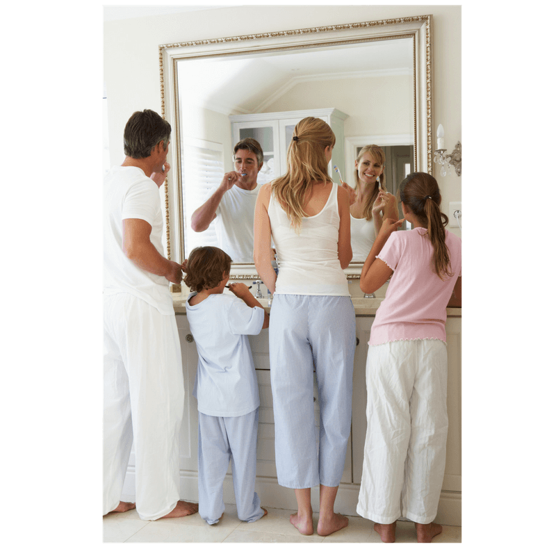 family of mom, dad and 2 kids bushing teeth together