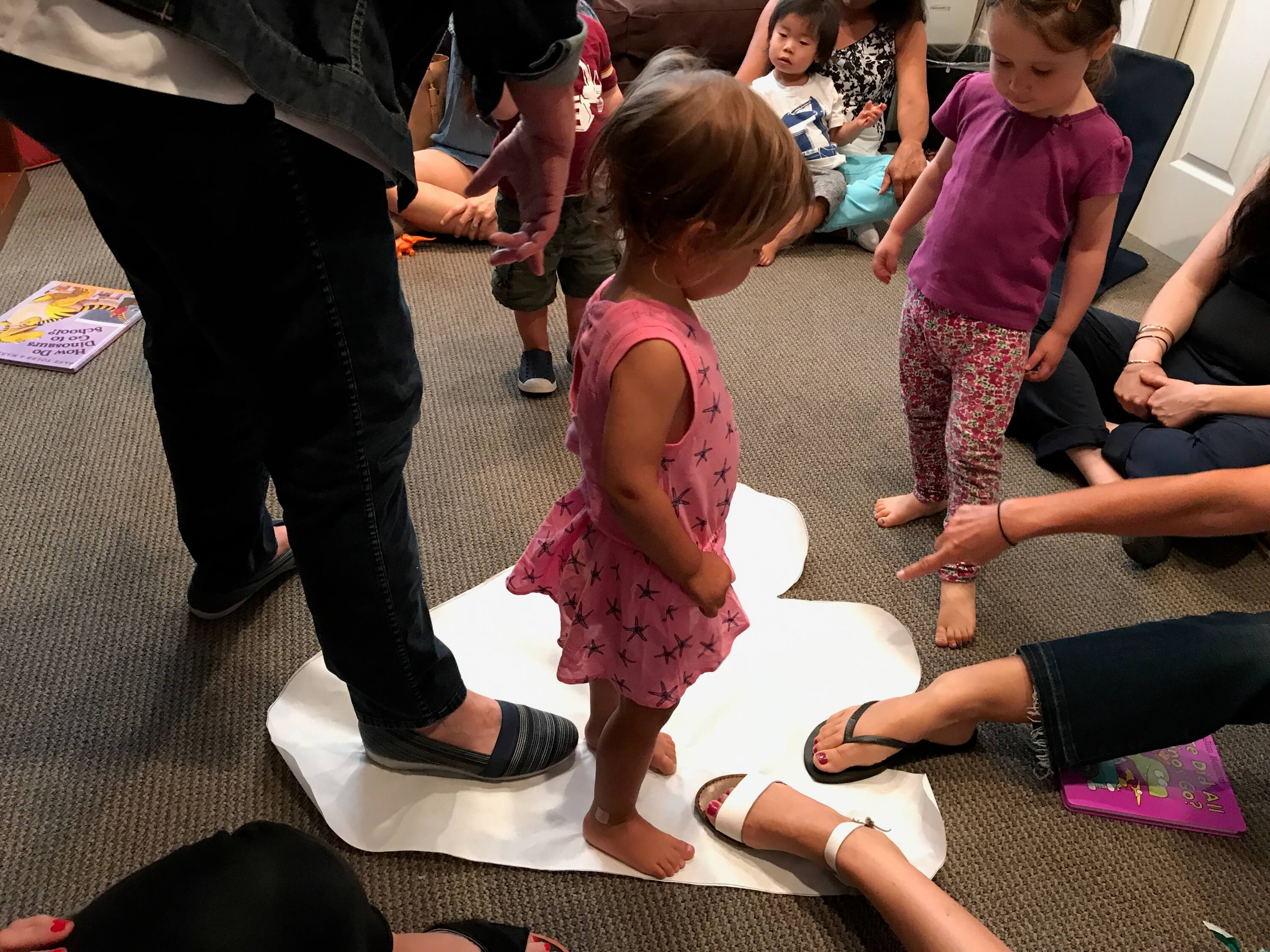 toddler measuring sizes of feet comparing to pig dinasour print on the floor at Early Childhood Development Associates's preschool prep class