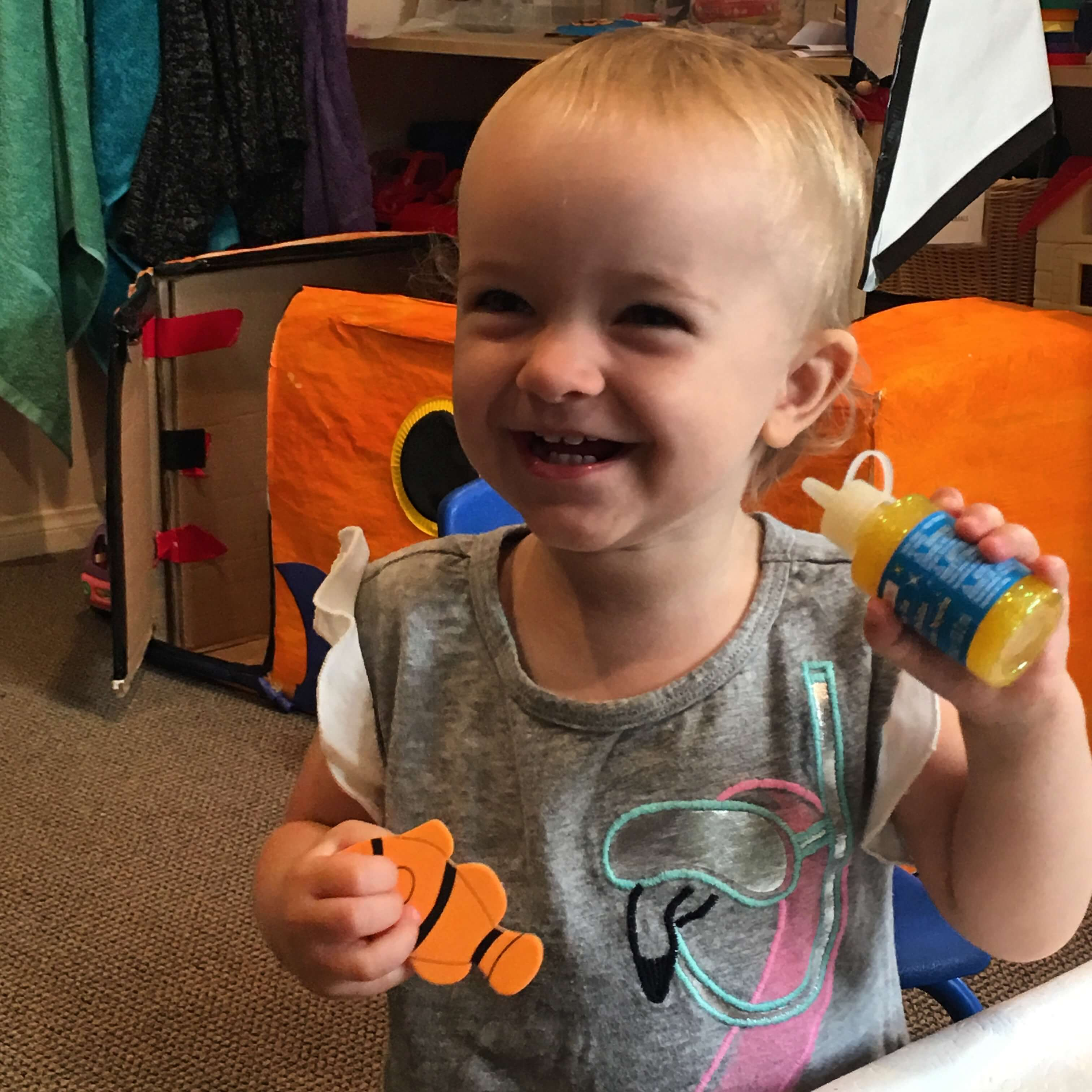 toddler smiling wiht a sticker of a fish and glue to decorate her boat at Early Childhood Development Associates' class