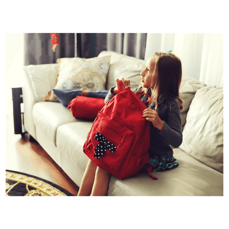 little girl setting up red backpack to go to school