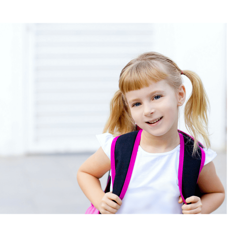 little girl looking happy wearing her backpack and ready to go to school in the morning