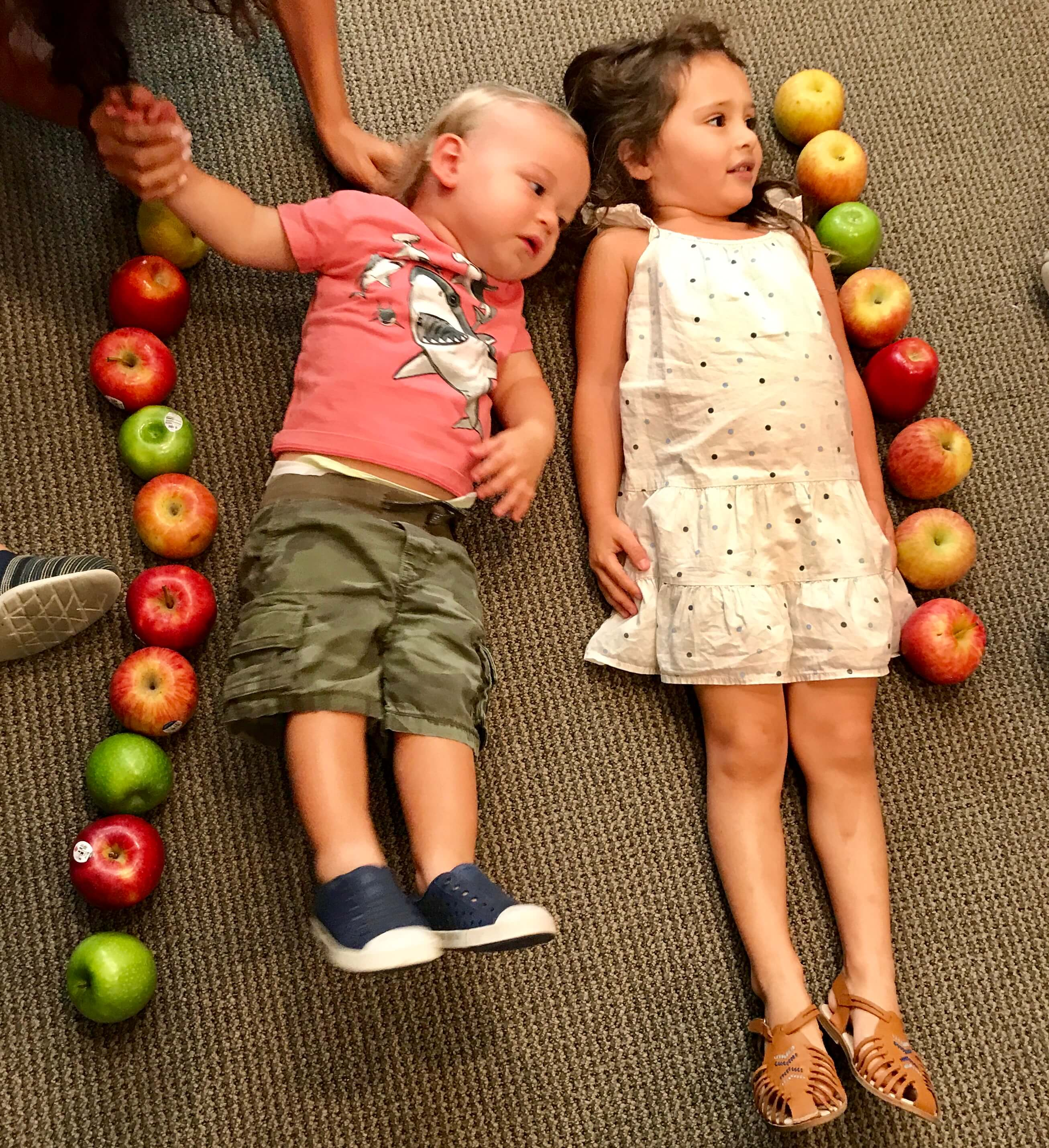 2 toddlers luong on the floor with apples beside them in the form of a line to measure their height with the apples at ECDA