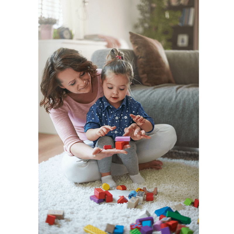 mother and toddler girl playing with woden blocks on the floor